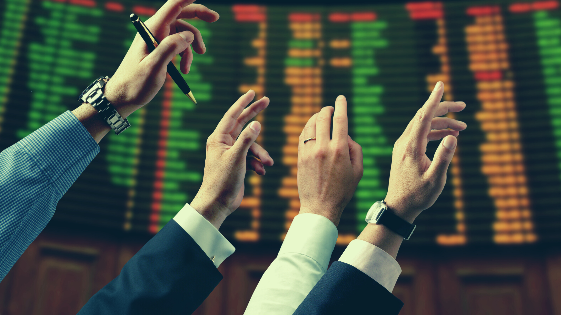 traders raising their hands